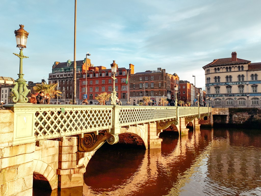 An old bridge in Dublin Ireland with buildings in the background on a sunny day