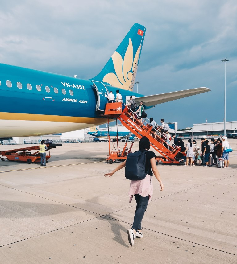 a women walking to a Vietnam Airlines flight in Ho Chi Minh, City