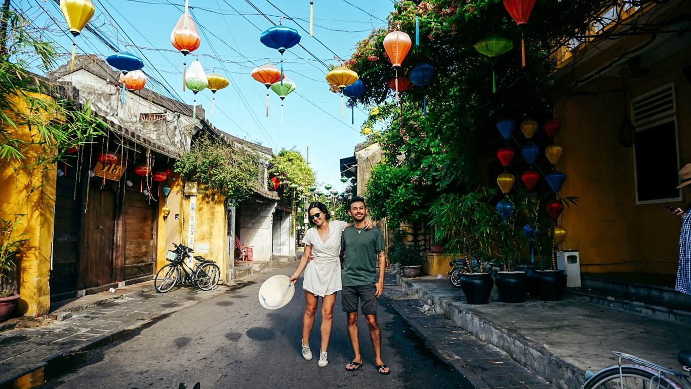 A couple posing together in a colorful, lantern street of Hoi An, Vietnam