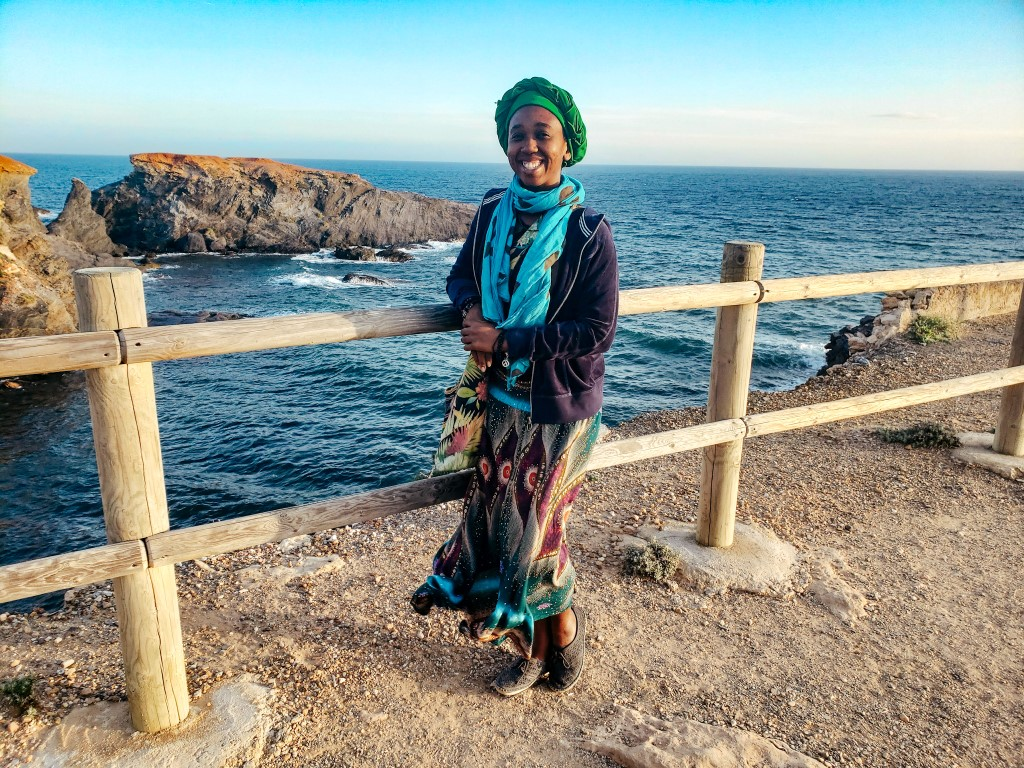 A Black American women enjoying smiling over a railing on the rocky coast of Spain