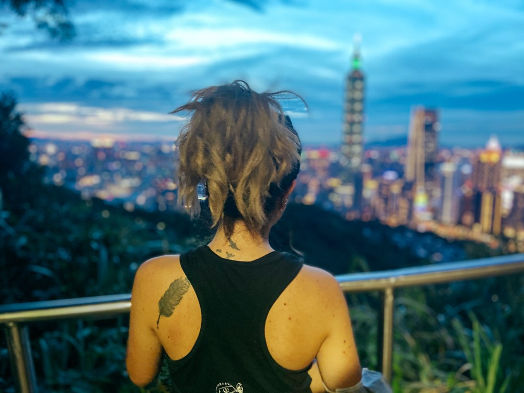 A view of Taipei's skyline at sunrise with the backside of a woman in the foreground