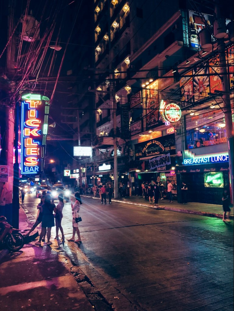 A picture at night in Poblacion, Manila with the neon lights and a group of women talking in the street