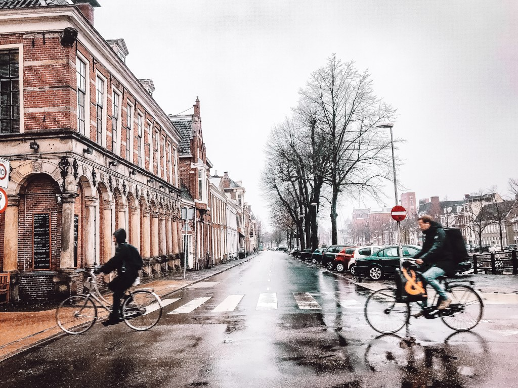 A misty day in Groningen, Netherlands with people riding by on the bicycles and rain gear.