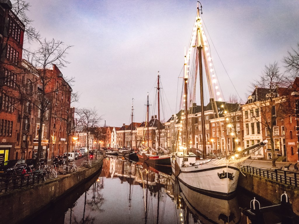 A sunset view of a canal street in Groningen and the boat up front has been decorated with big white bulbs