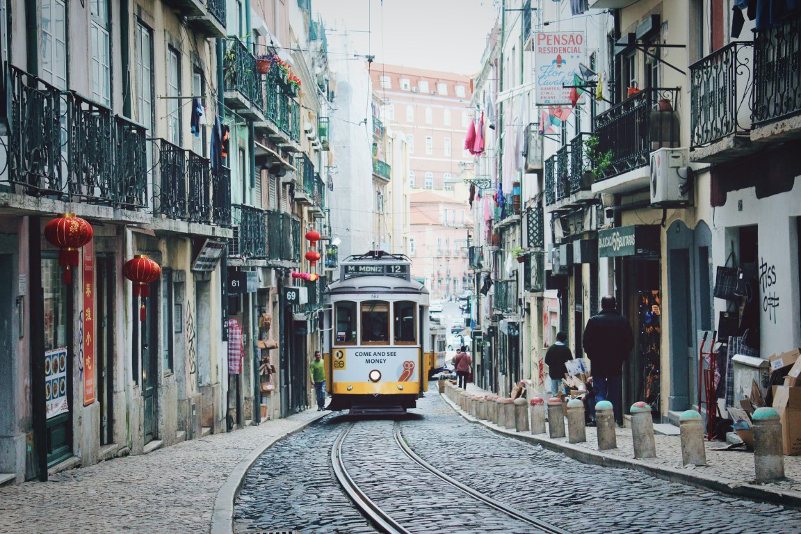 A street view of Lisbon's iconic tram going through a cobblestone street in the aftenoon