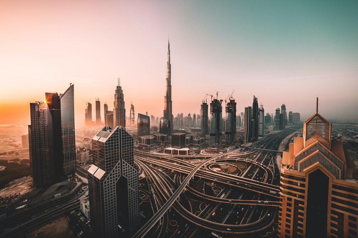A pink sunset overlooking the center of Dubai with giant skyscrapers and the huge highway system apparent