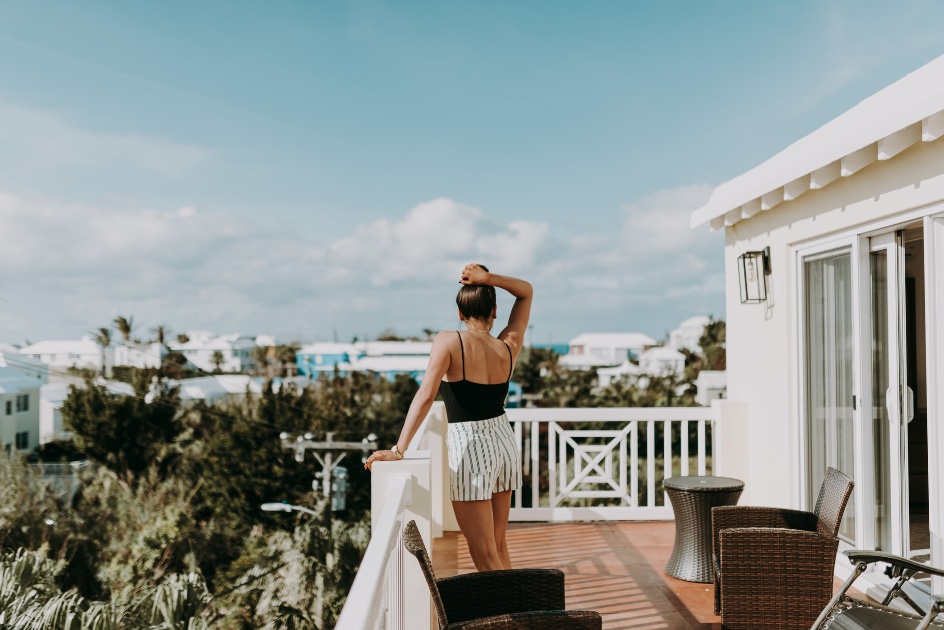 A woman's back as she stands on her rooftop patio overlooking the roofs of her neighbors homes in Bermuda