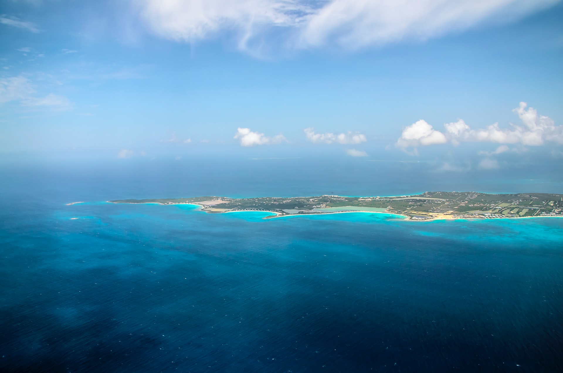 Anguilla from a plane showcasing the small island and the deep blue ocean surrounding it