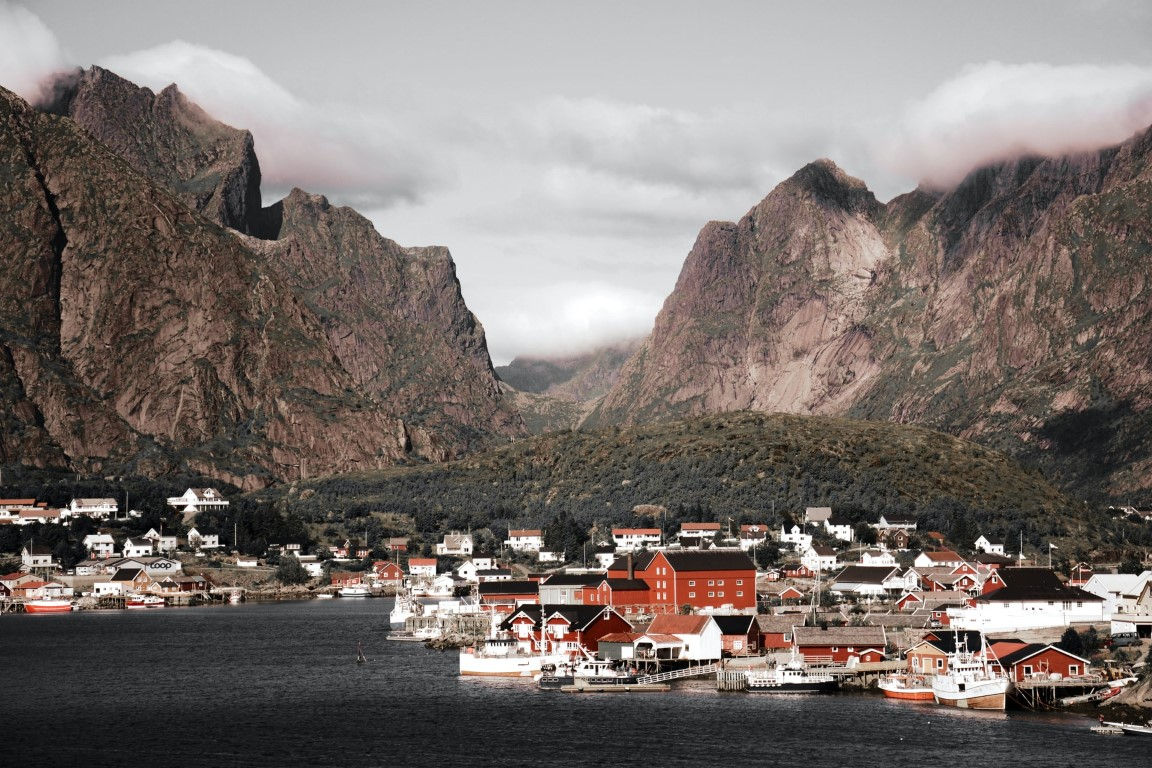 A spectacular view of a small Norwegian town sitting on the water with steep mountains in the backdrop