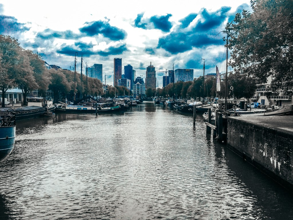 A cloudy day in Rotteram with a view of the canals but the city center in the background