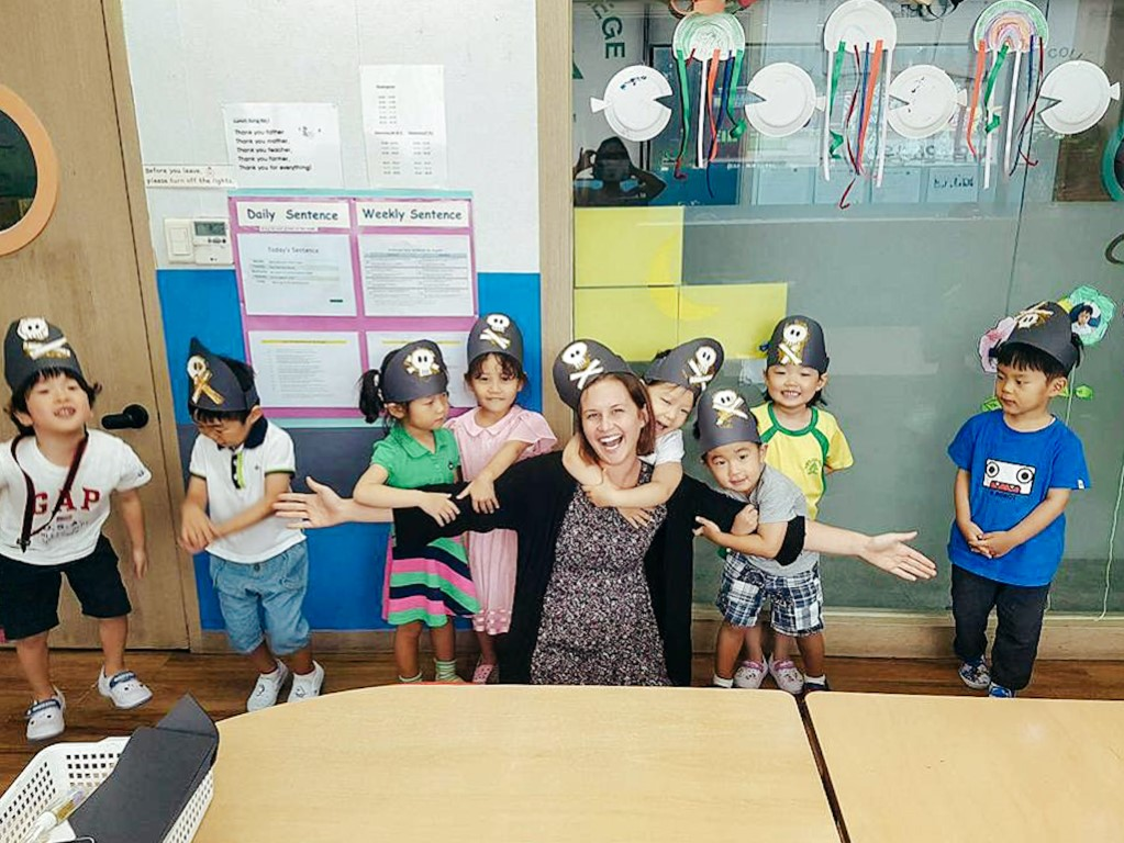 A smiling English teacher posing with her young students, all wearing handmade pirate hats