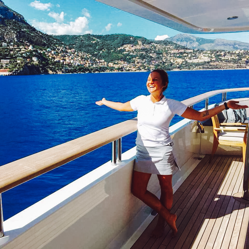 A smiling woman posing in her yacht stew uniform on the side deck with Monaco in the background