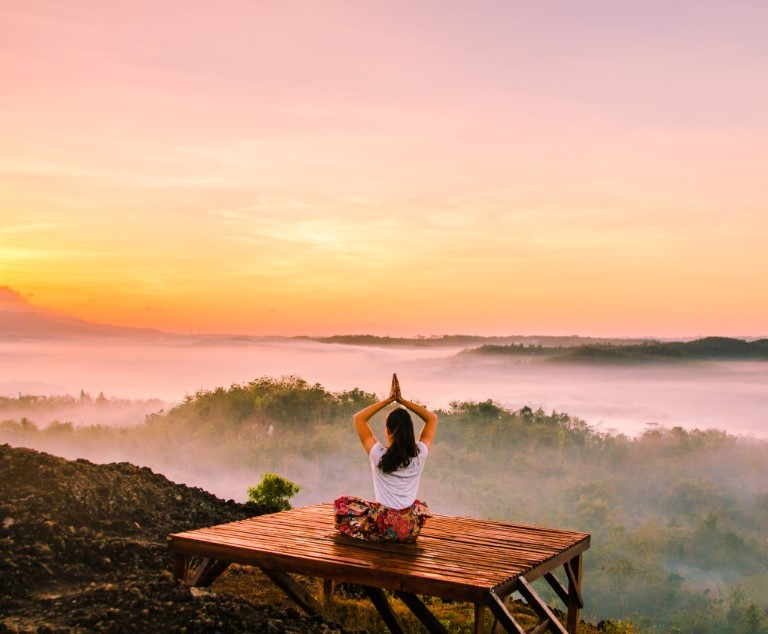 A beautiful sunrise with a woman doing yoga on a platform enjoying the peaceful morning