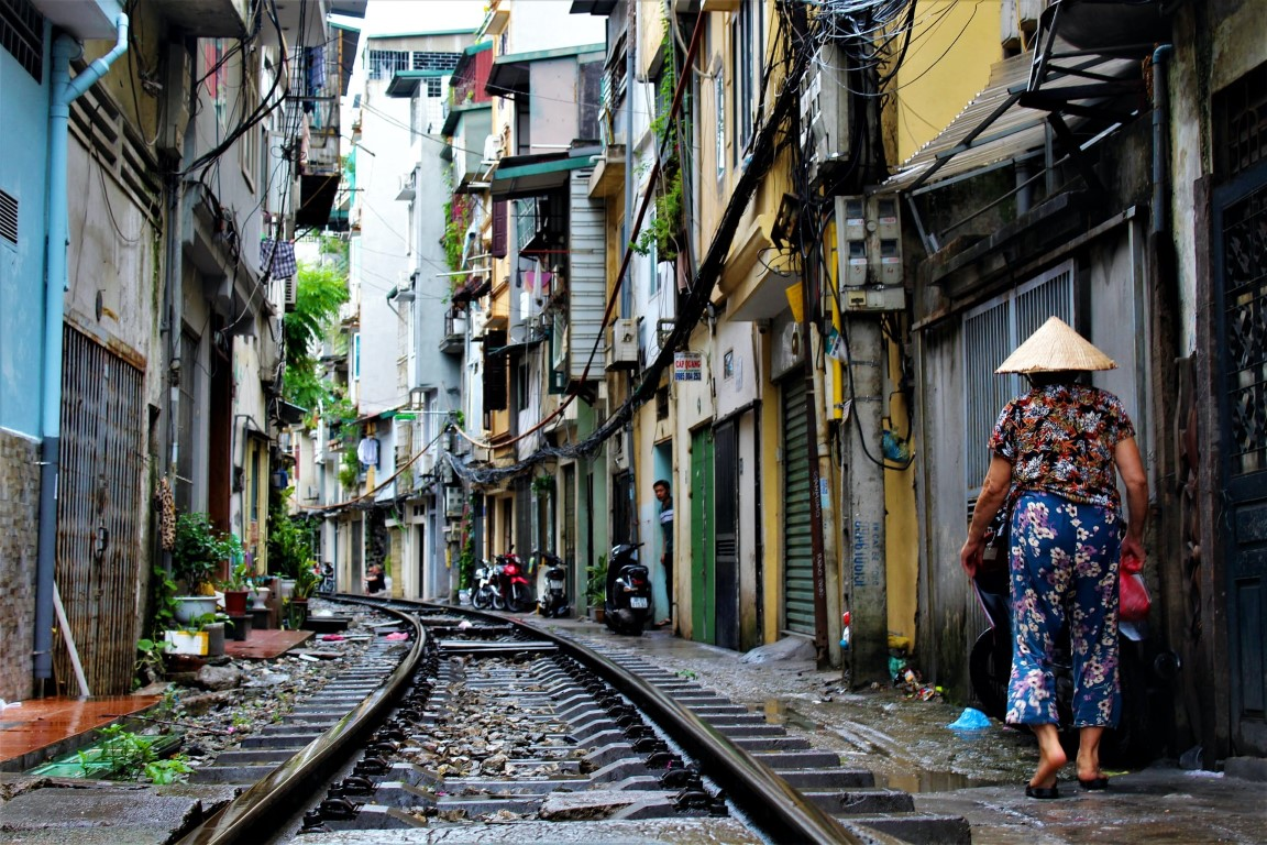 Hanoi, Vietnam's famous train street with a woman walking by in a conical hat