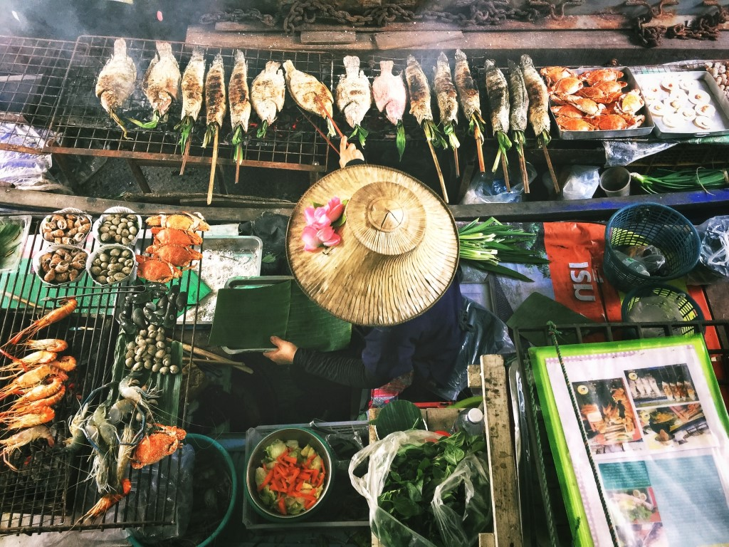 Overhead view of a woman single-handedly cooking a Thai feast