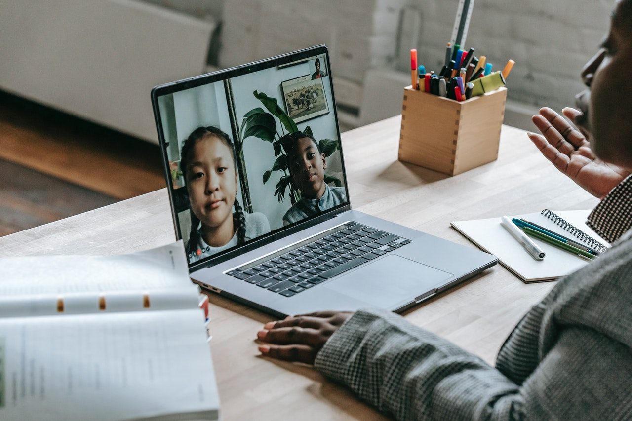 A woman teaching online to two engaged students from her home.