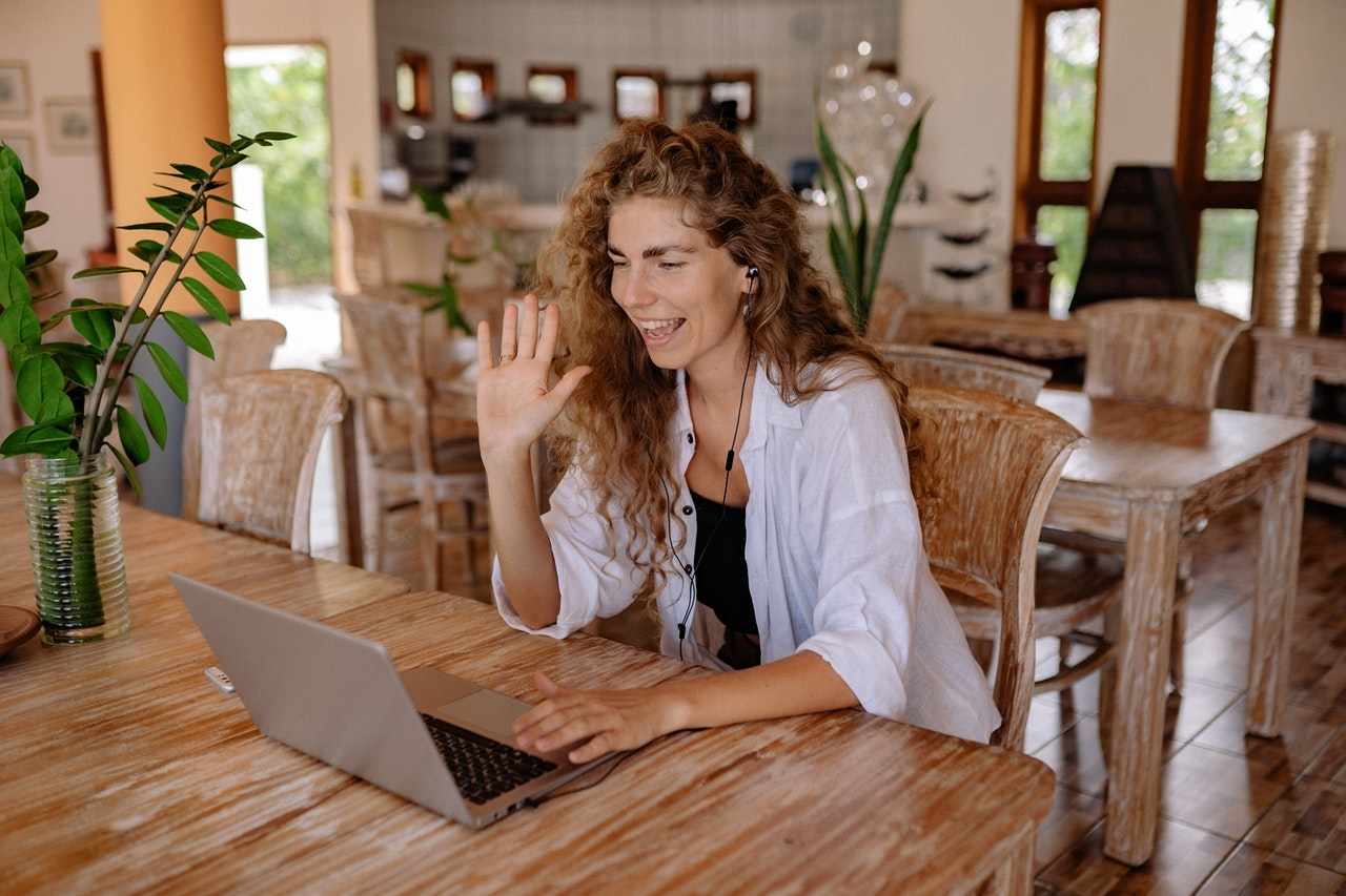 A woman waving to the camera on her computer as she starts a client call from her living room