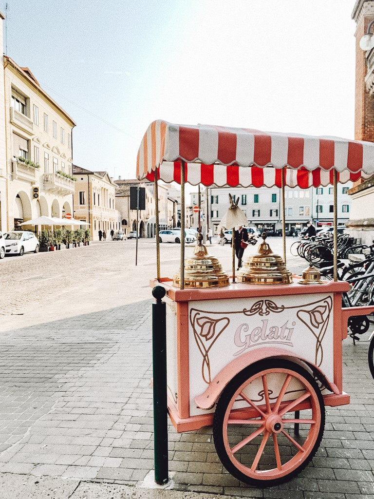Italian aesthetic gelato cart parked in a plaza in Treviso, northern Italy on a sunny day