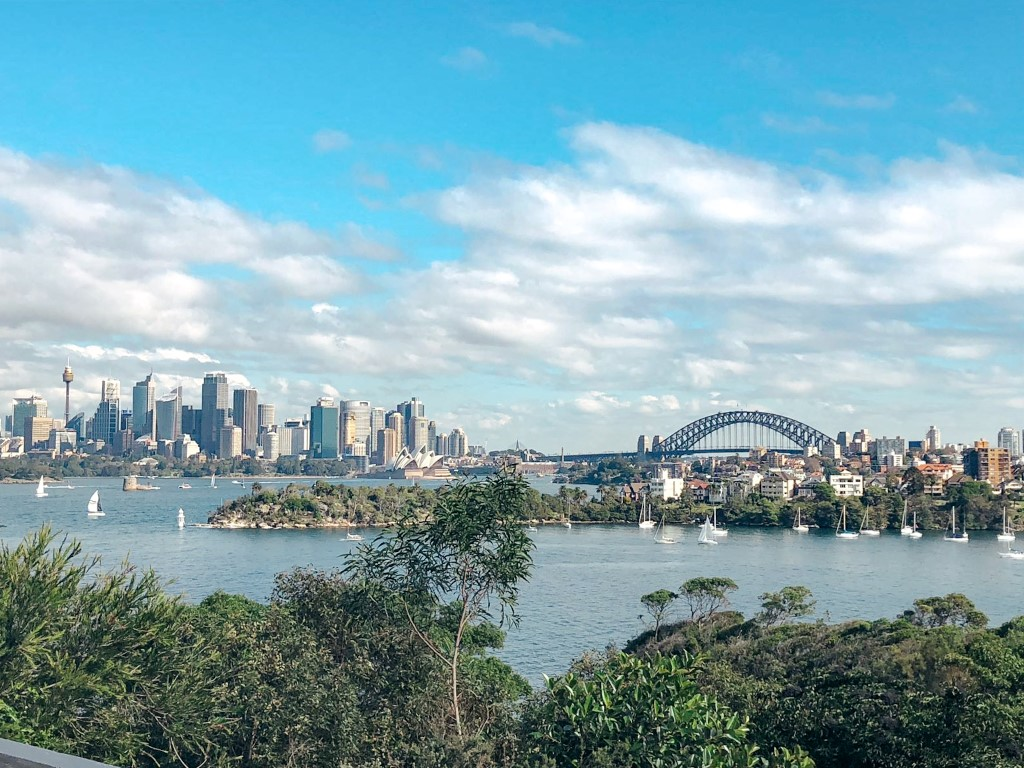 A skyline view of Sydney, Australia on a sunny afternoon with the water, opera house and blue skies