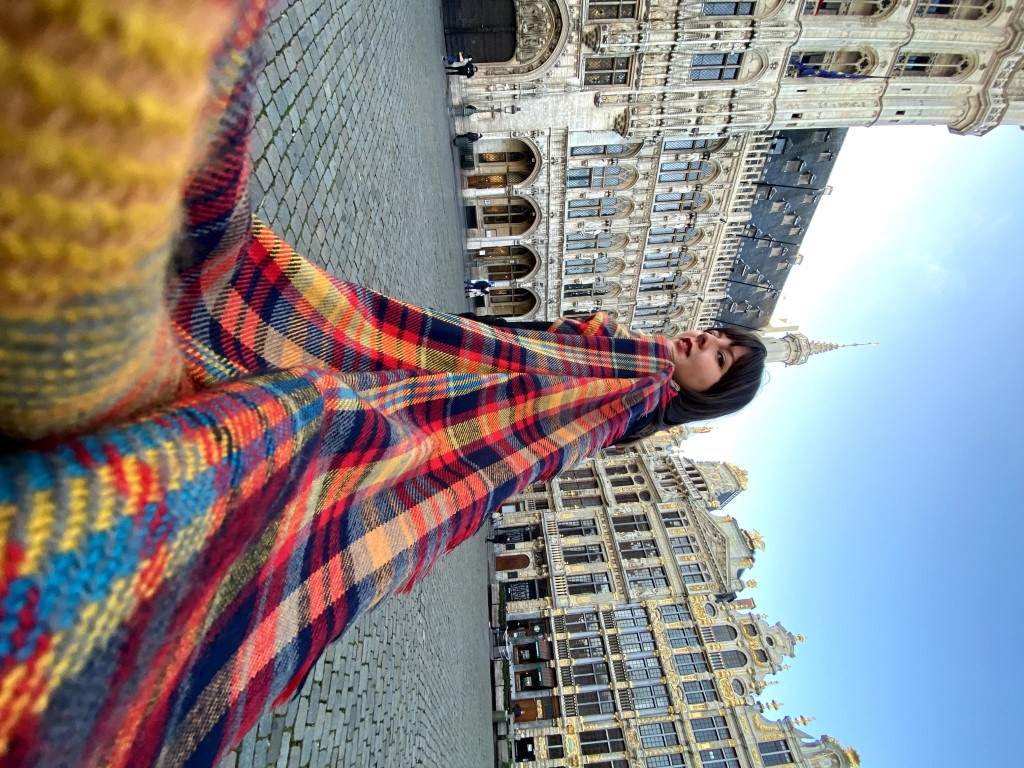 A female expat living abroad in belgium looking back at the camera with a bright, checkered scarf wrapping back to the camera