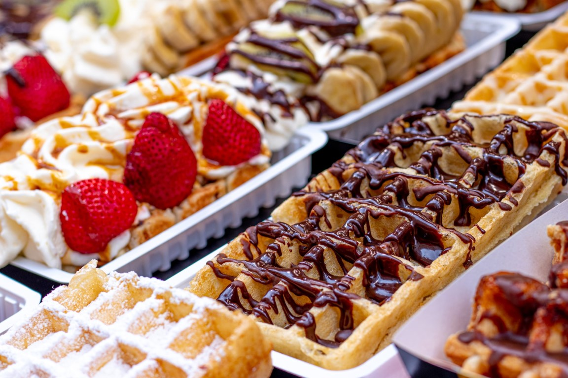 A close-up image of Belgium waffles with chocolate syrup, whipped cream and strawberries