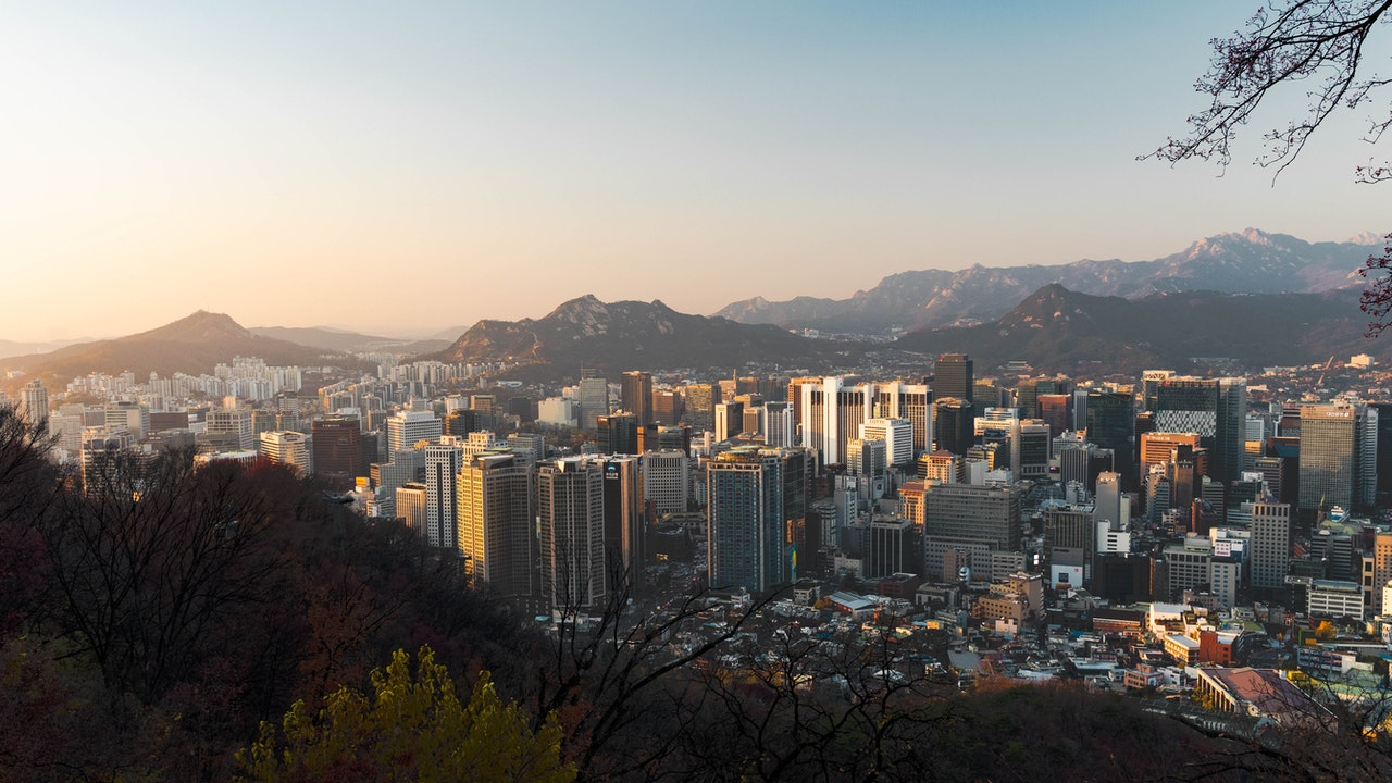 Seoul, at sunset, with the city sprawling out on the landscape and mountains mixed in with the city