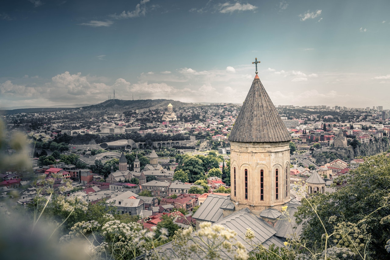 sunny afternoon view of Tbilisi, Georgia with a church steeple in the foreground