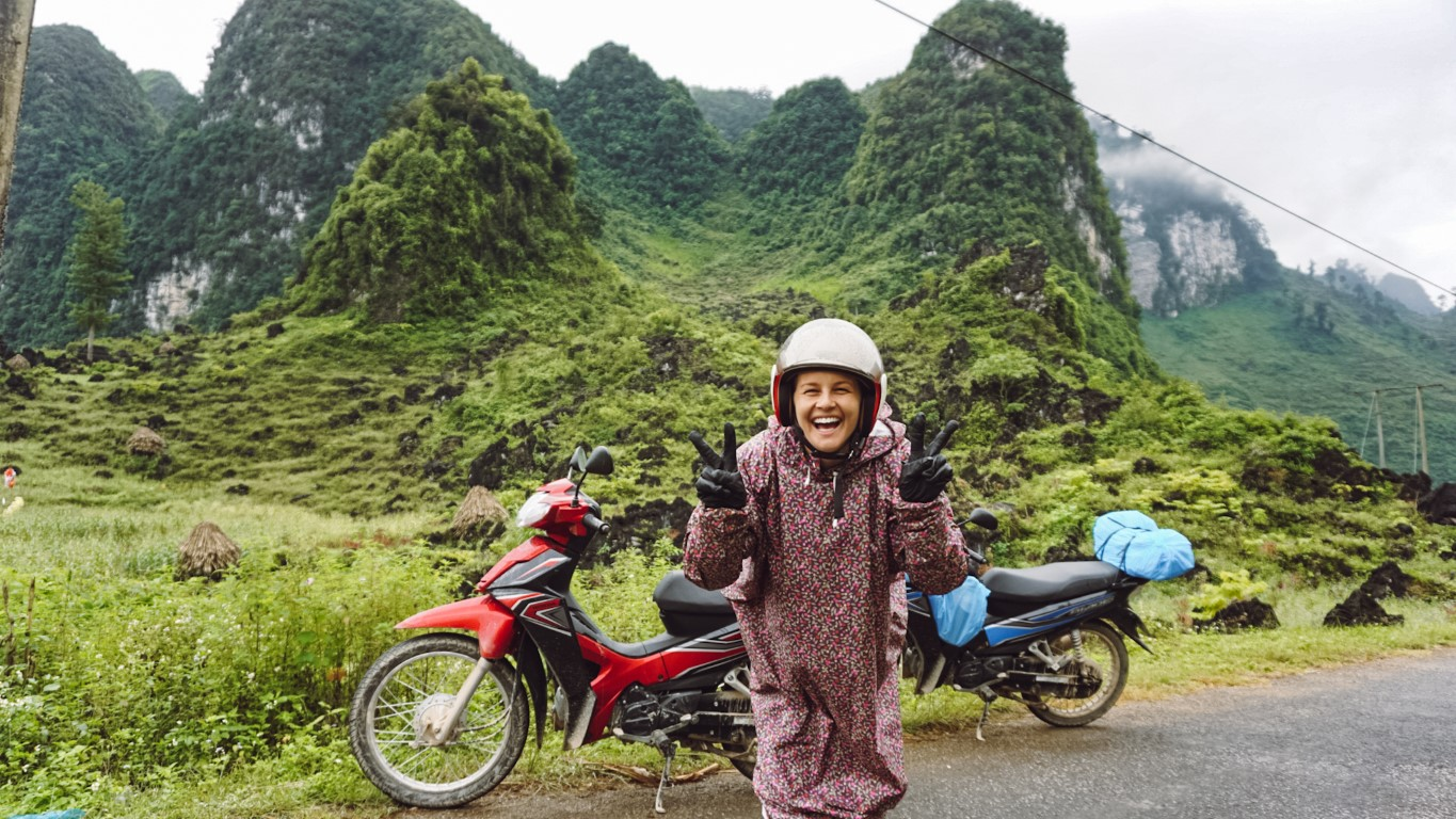 A smiling woman giving a peace sign in front of two motorbikes parked in front of green limestone mountains in Ha Giang, Vietnam