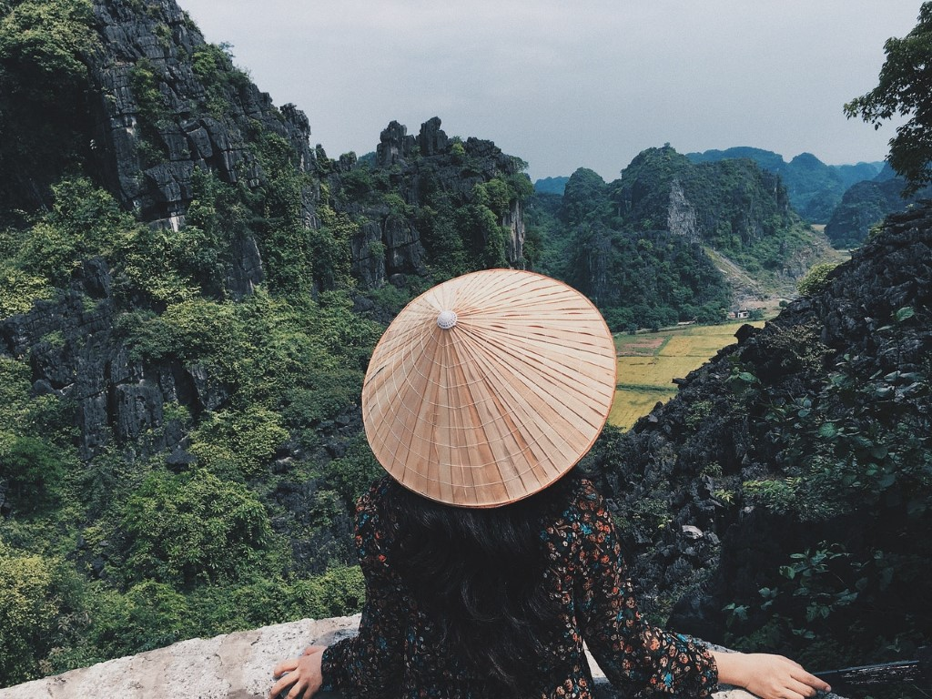 a woman wearing a conical hat overlooking the limestone mountains in ninh binh, vietnam