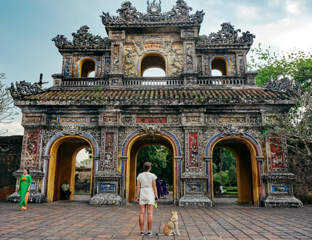 a woman and her dog looking up at an entrance of the imperial city, hue, vietnam