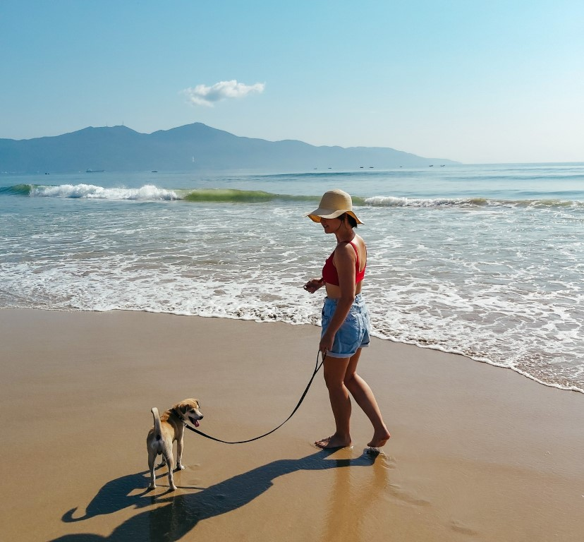 a woman wearing a swimsuit and beach hat taking a walk down the beach with her dog in Da Nang, Vietnam