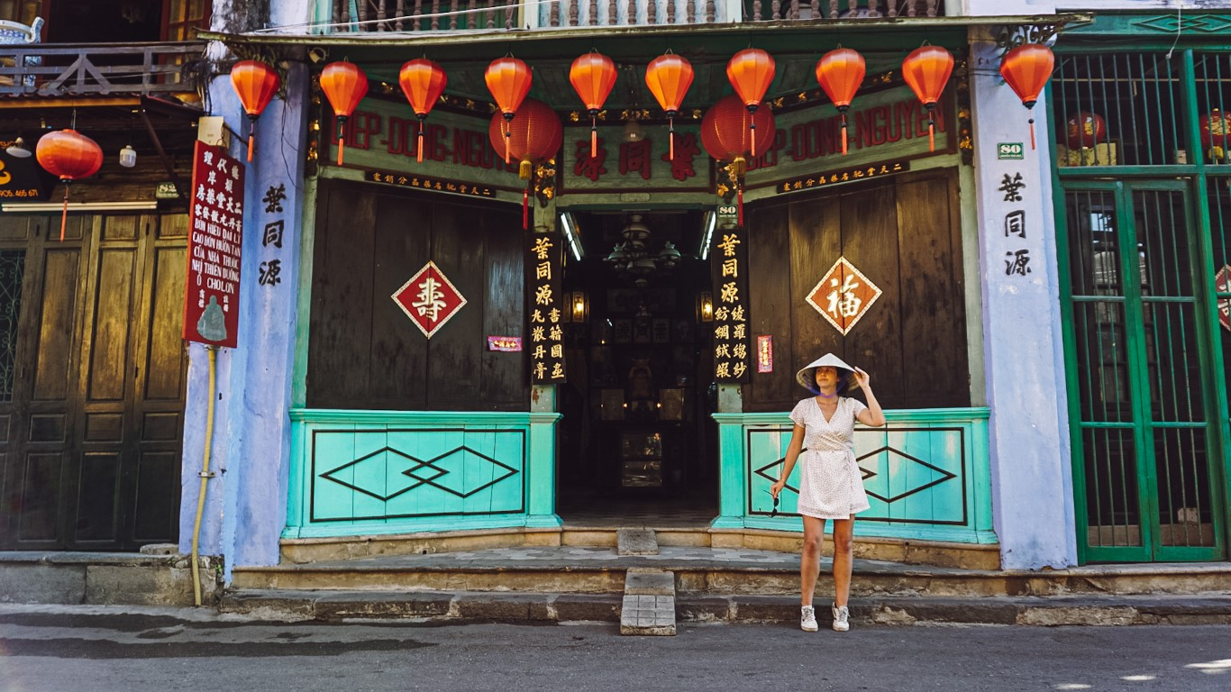 a woman posing in front of a chinese medicine shop in hoi an, vietnam