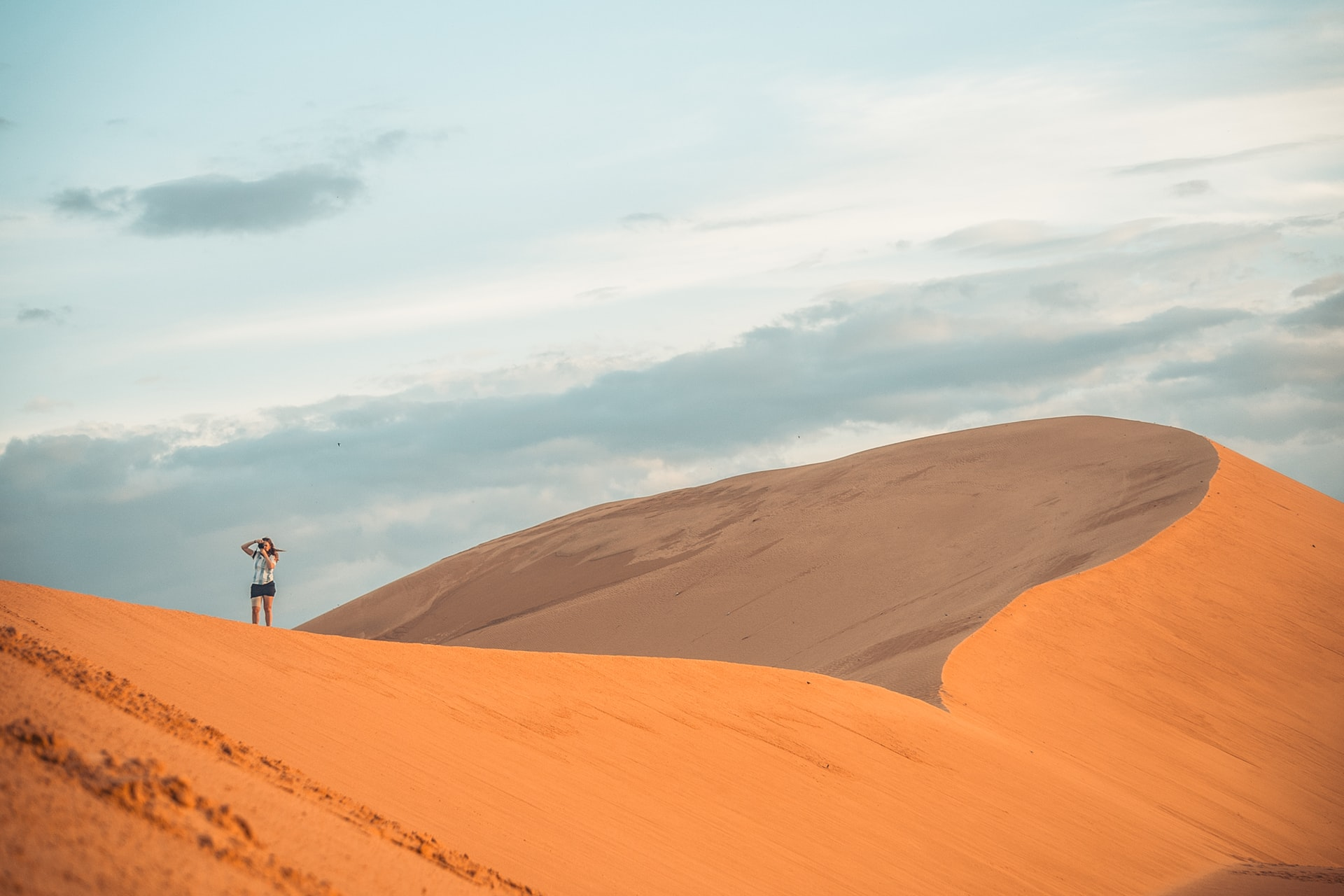 a view of the sand dunes in Mui Ne with one woman standing on the dunes, taking a picture