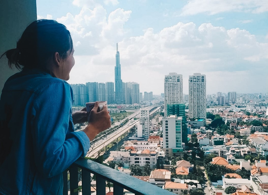 a woman overlooking Ho Chi Minh City from her balcony while drinking a coffee