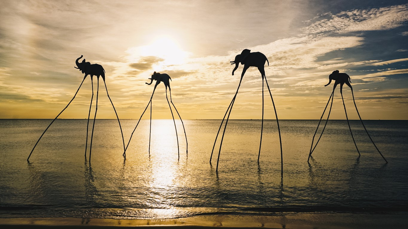a Dali-inspired art on the shoreline of Phu Quoc with 4 elephants with long legs in front of the setting sun