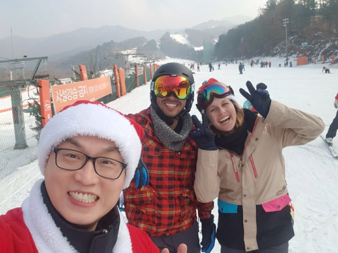 Three smiling friends snowboarding on Christmas in South Korea