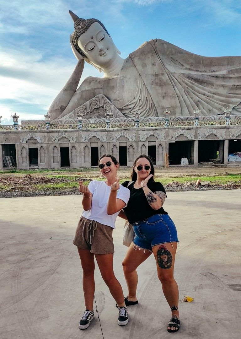 Two smiling friends posing in front of the giant laying down Buddha statue in Soc Trang, Vietnam