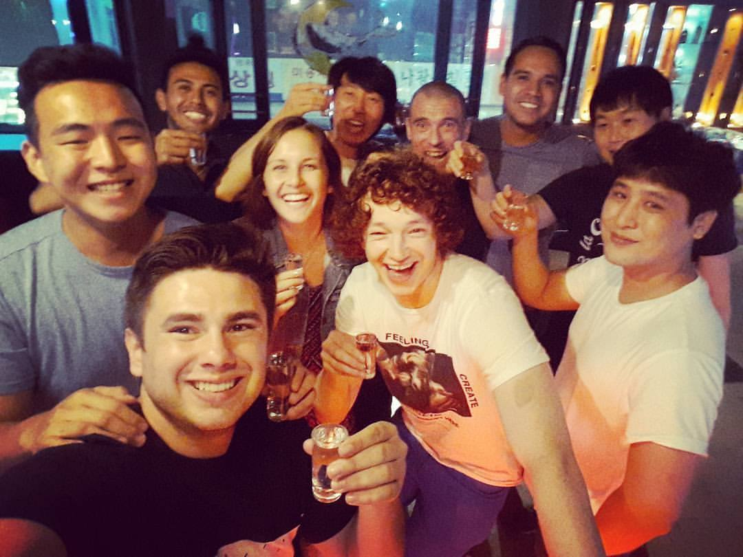 A group of people all with shots in their hands smiling for a selfie in a bar in South Korea