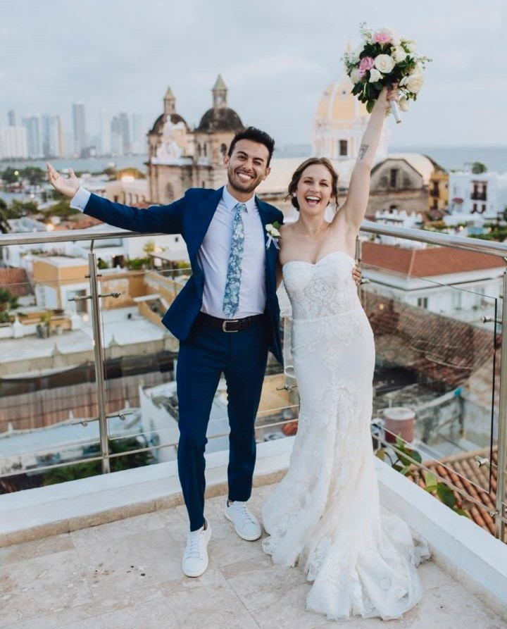 A smiling married couple posing on a rooftop in Cartagena, Colombia