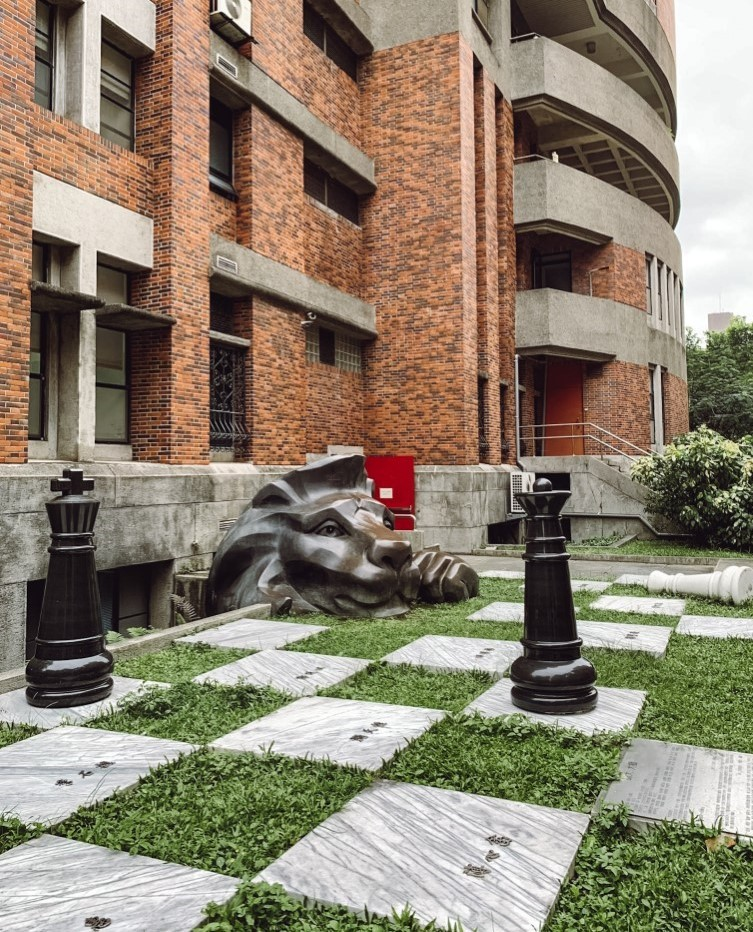 View of Shida campus in Taiwan with a brick building and a lion statue on a giant chess board