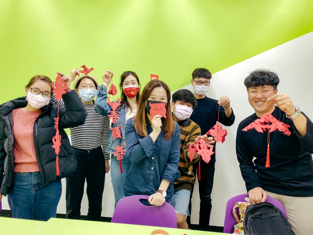 a group of students studying Chinese in Taipei holding up their Lunar New Year decorations