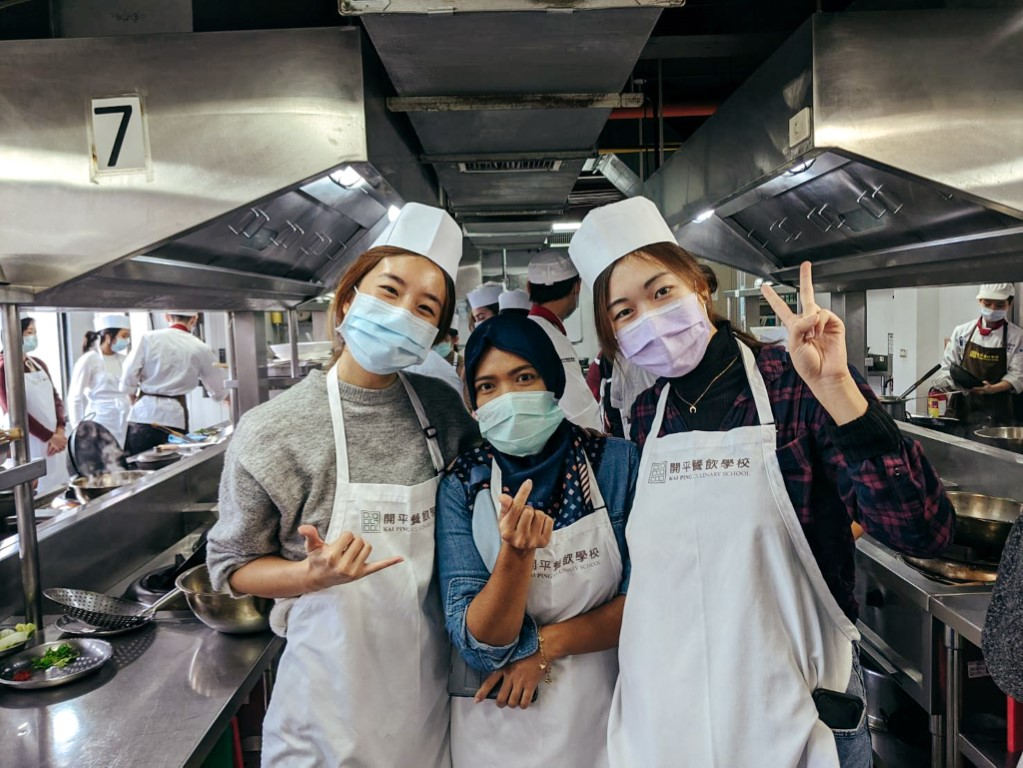 Students in Taipei taking a culinary class posing for the camera in the kitchen