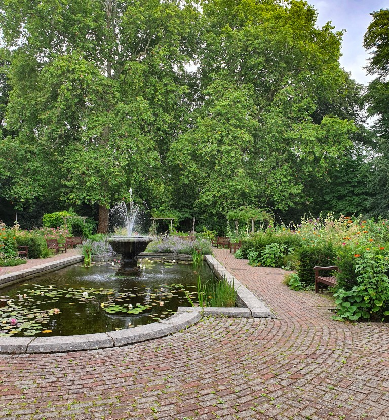 A green park with trees and flowers surrounding a fountain on a brick sidewalk