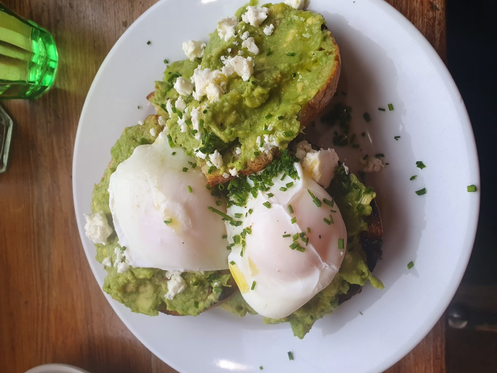 Breakfast with smashed avocado toast, poached eggs and feta cheese in London