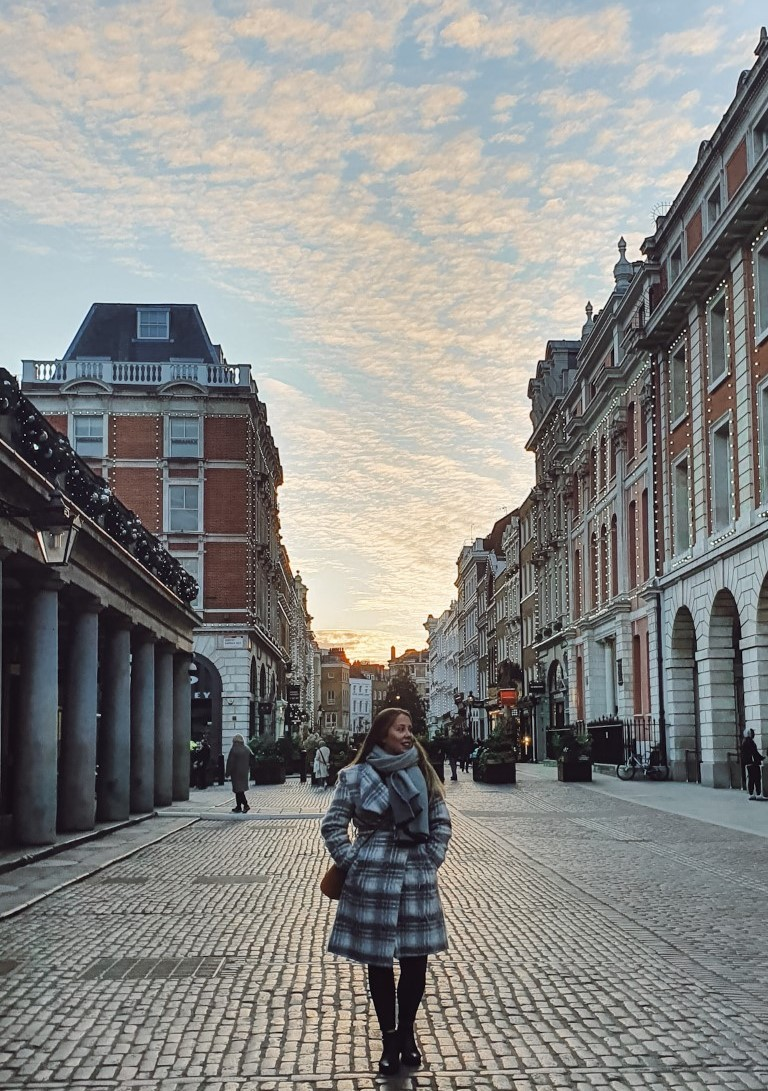 A woman posing on a quiet street in London during sunset with pink clouds on a blue sky