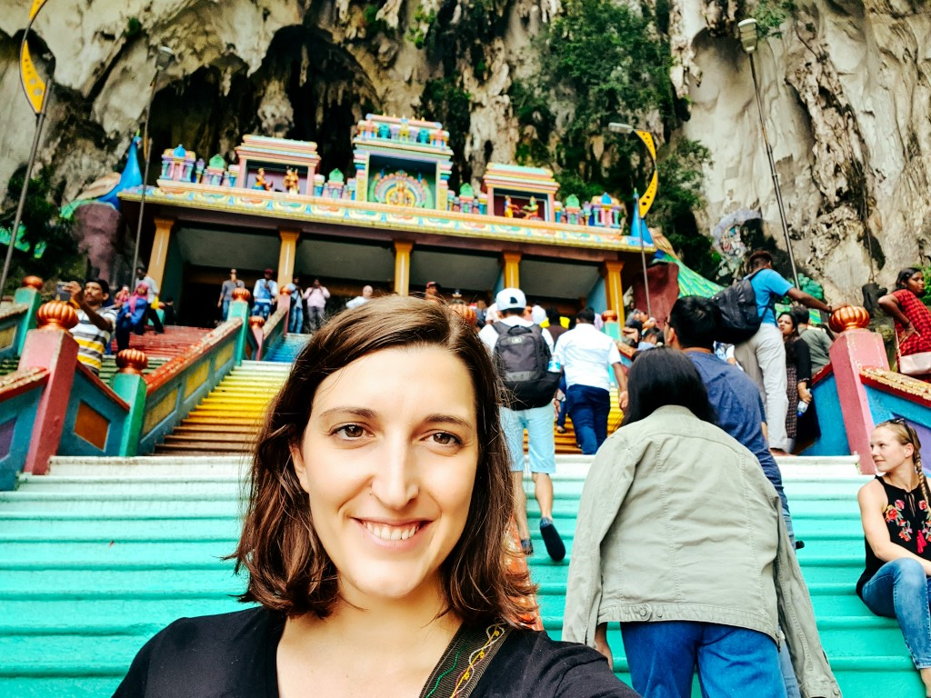A woman taking a selfie on the rainbow stairs leading up to Batu Caves in Kuala Lumpur