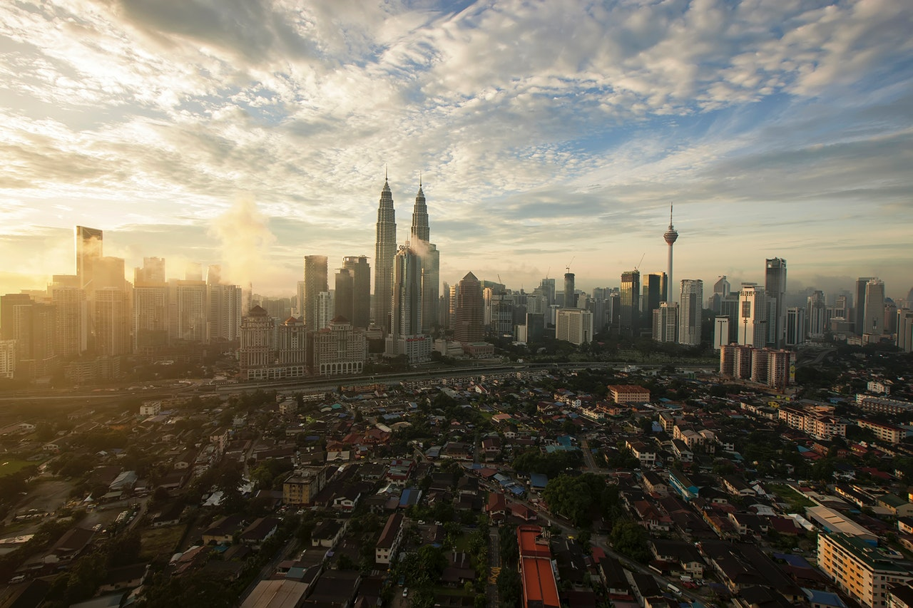 a view of Kuala Lumpur from a rooftop during sunset with the entire city in view