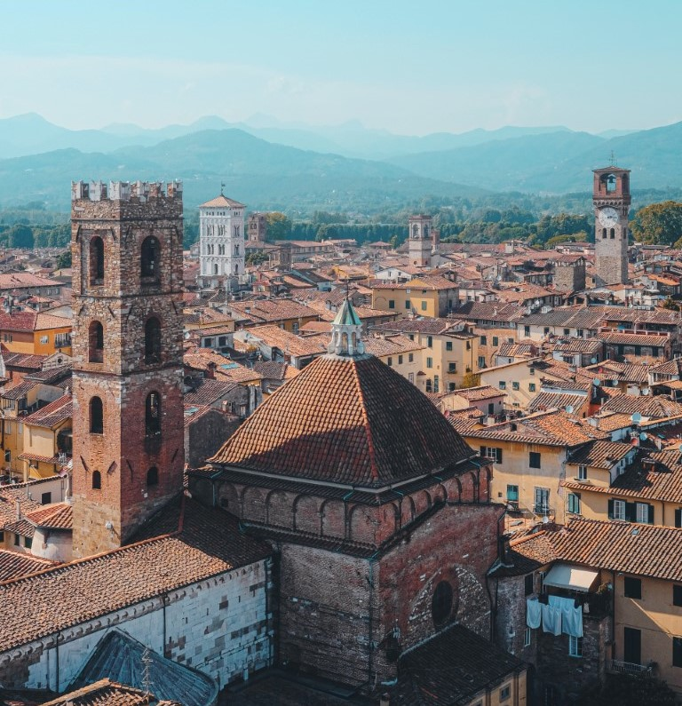A view of Lucca, the walled city, with it's red roofs and mountains in the background