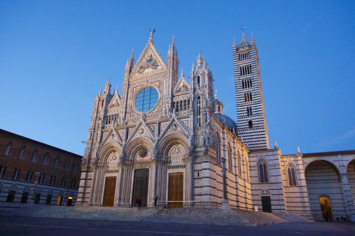 The Duomo di Siena, a white and black Cathedral, at dusk on a clear night