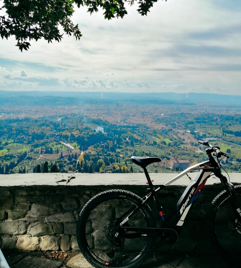 A bike leaning against a stone wall overlooking Fiesole, Italy below